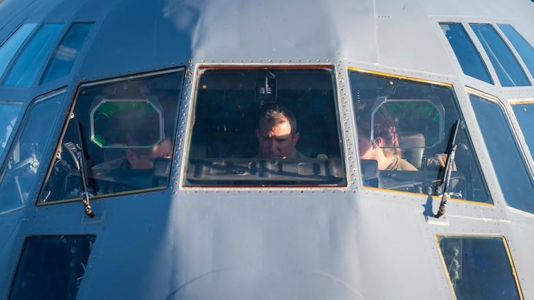 Airmen prepare pre-flight checks of a C-130J