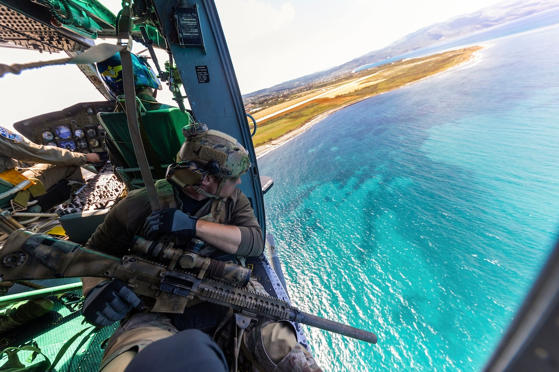 A soldier looks at a body of water from the open door of an airborne helicopter.