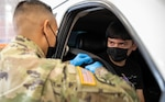 Service member administers COVID-19 vaccine to teen from car