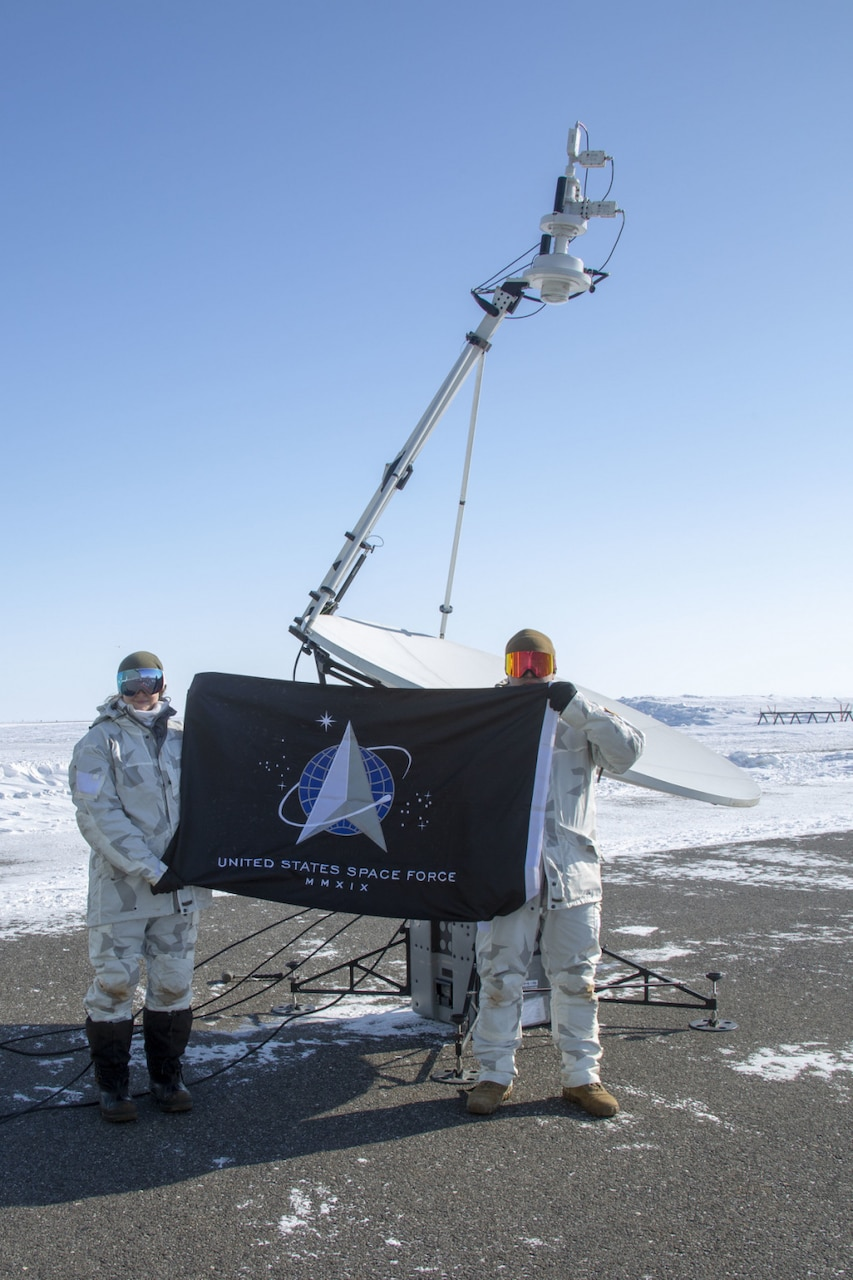 Two Space Force guardians stand in front of a satellite while holding a flag.