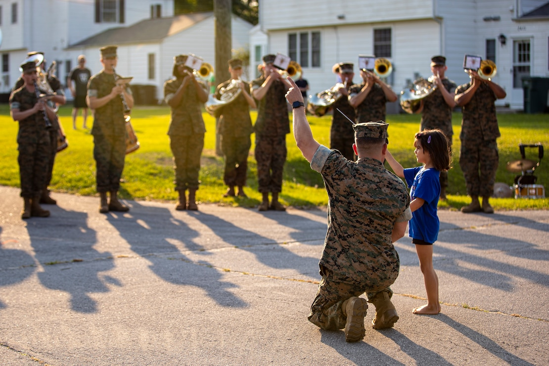 U.S. Marine Corps Chief Warrant Officer 2 Stephen Howell, a native of Hernando, Miss. and the band officer of the 2d Marine Division Band, shows a member of the community how to conduct on Camp Lejeune, N.C., May 20, 2021. The band performed several neighborhood concerts throughout the month of April and May in various locations across base to enhance the morale and sense of community. (U.S. Marine Corps photo by Lance Cpl. Jacqueline Parsons)