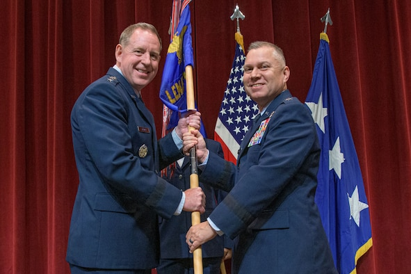 Lieutenant Gen. James B. Hecker (left), commander and president, Air University, passes the guidon to Maj. Gen. William G. Holt II at Maxwell Air Force Base, Alabama, May 24, 2021.