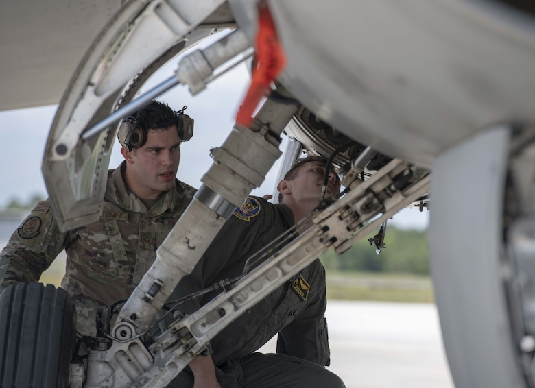 A photo of Airmen looking into a jet.