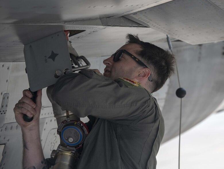 A F-16 pilot works on a jet.