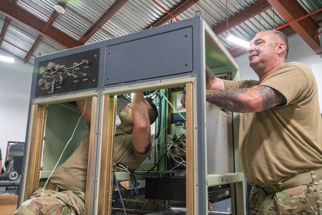 """Senior Airman Warren Reynier and Master Sgt. Alexander Mitchell, 403rd Maintenance Squadron meteorology technicians, work on the internal wiring of the aerial reconnaissance weather officer station at Keesler Air Force Base, Miss., May 12, 2021. The 53rd Weather Reconnaissance Squadron """"Hurricane Hunters'"""" ARWO and loadmaster/dropsonde operator stations are being upgraded with hardware and software to increase their weather collecting capabilities. (U.S. Air Force photo by 2nd Lt. Christopher Carranza)"""