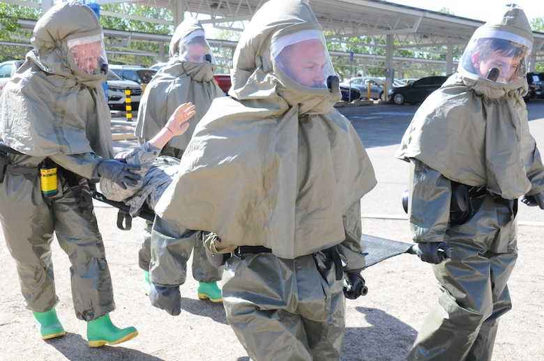 Military medics carry a simulated patient on a litter.