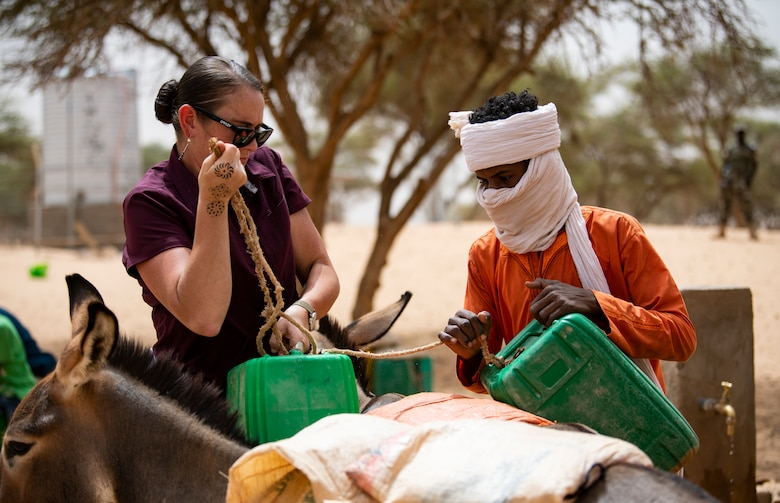 U.S. Army Staff Sgt Cana Garrison, with the 411 Civil Affairs Battalion, stationed at Air Base 201, helps a local Nigerien attach water jugs filled by a solar powered well to their donkey to transport back to their home.  (U.S. Air Force photo by Tech. Sgt. Perry Aston)