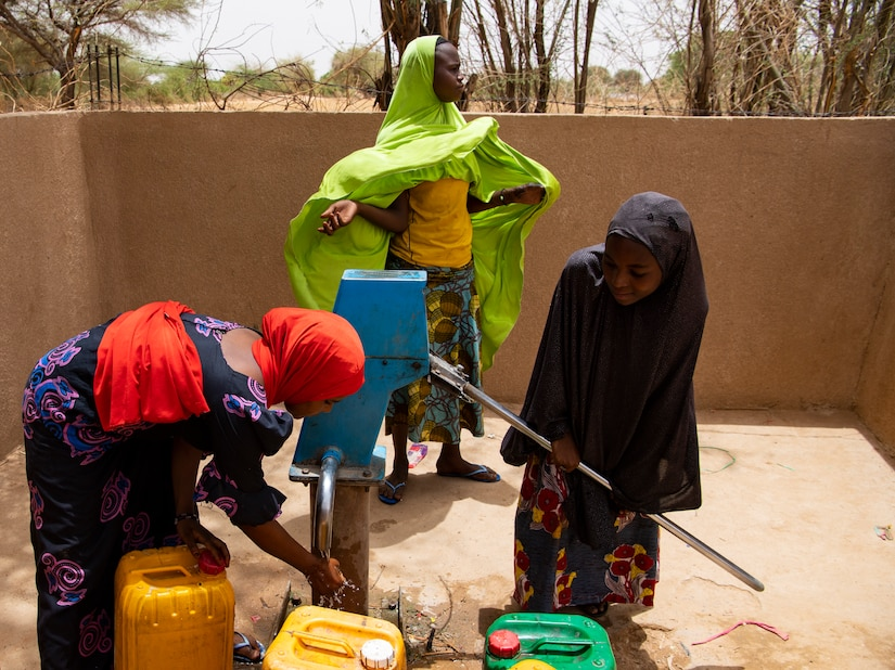 Nigerien women pump water into containers at the village well. The well is currently being converted into a solar powered well, to eliminate the need to hand pump water. (U.S. Air Force photo by Tech. Sgt. Perry Aston)