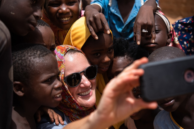 U.S. Army Staff Sgt. Cana Garrison, Civil Affairs Team 204, takes a selfie with Nigerien children at a village in Agadez, Niger, June 27, 2019. The civil affairs team reaches out to the local community on a weekly basis to strengthen the relationship between the Nigeriens and the U.S. military. (U.S. Air Force photo by Staff Sgt. Devin Boyer)