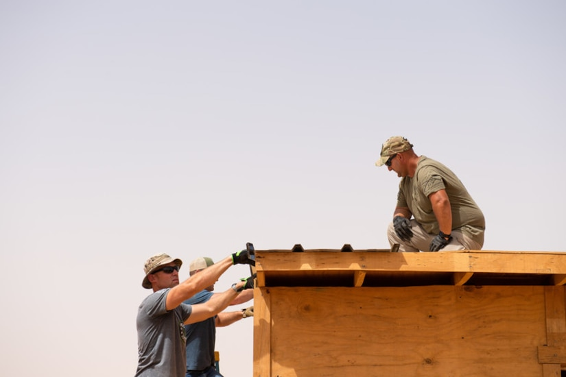 Airmen assigned to the 724th Expeditionary Air Base Squadron civil engineer flight install tin roofing on a classroom at a village in Agadez, Niger, June 27, 2019. The Airmen built the entire classroom using leftover wood from Air Base 201 and topped it off with locally purchased tin for the roof. (U.S. Air Force photo by Staff Sgt. Devin Boyer)