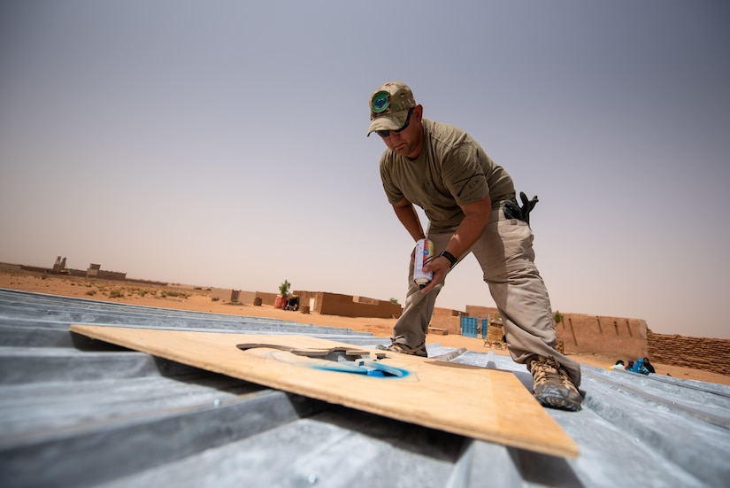 U.S. Air Force Tech. Sgt. Kelly Warren, 724th Expeditionary Air Base Squadron civil engineer flight structural craftsman, paints a bull head on the roof of a classroom at a village in Agadez, Niger, June 27, 2019. The civil engineers built the classroom from scratch and the bull is a symbol of the Prime Base Engineer Emergency Force, or Prime BEEF. (U.S. Air Force photo by Staff Sgt. Devin Boyer)