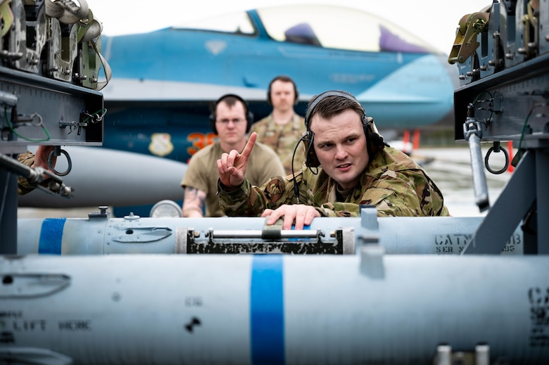 U.S. Airmen from the 18th Aircraft Maintenance Unit prepare an AIM-120 for pick-up during a load competition on Eielson Air Force Base, Alaska, May 21, 2021.