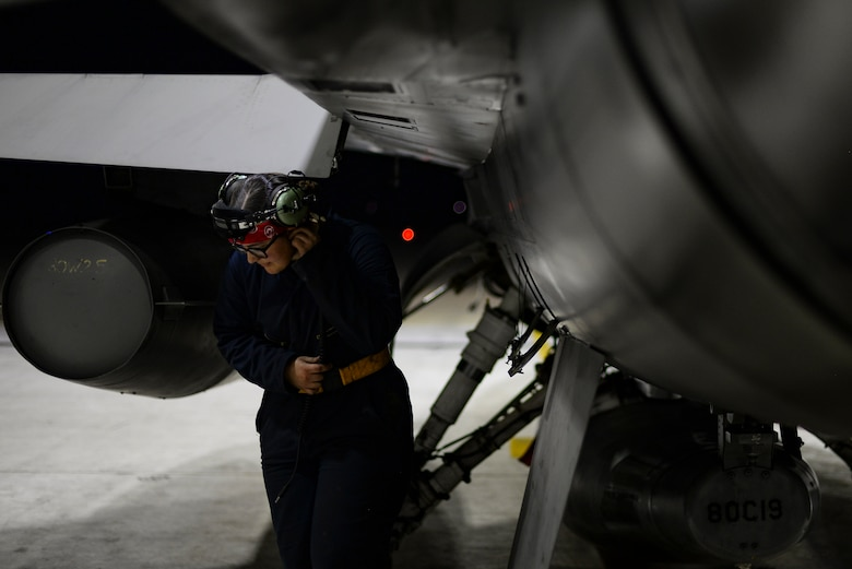 An Airman performs an inspection on a jet.