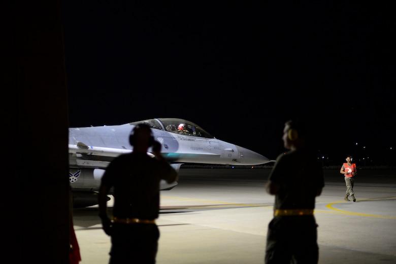 Flight chiefs supervise an Airman on the flight line.