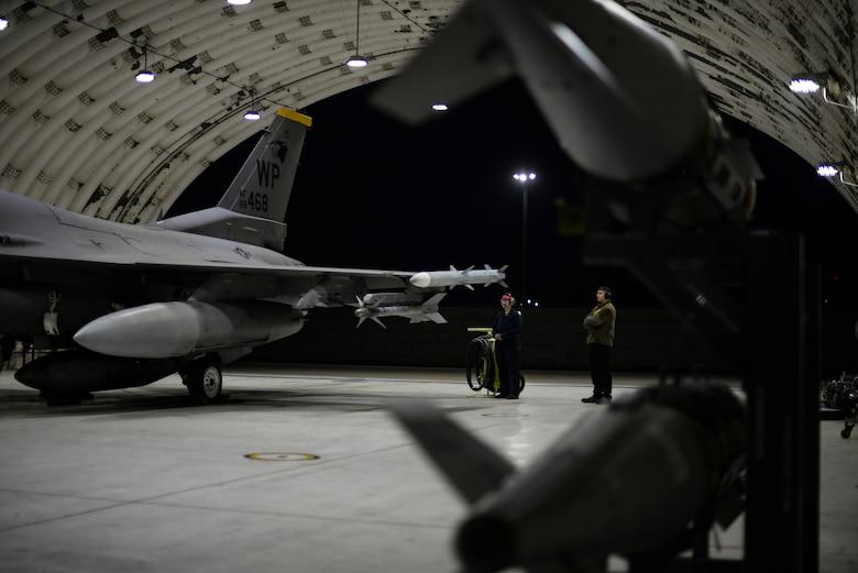 Airmen prepare a jet for flight.