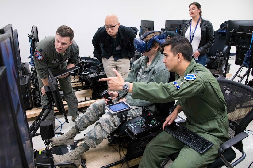 U.S. Air Force Capt. Orion Kellogg, Pilot Training Next instructor, discuses a future PTN version 3 student's virtual reality flight with members of NASA as part of a collaborative research agreement between Air Education and Training Command and NASA October 22, 2019, at Joint Base San Antonio-Randolph, TX. The goal of the agreement is to help both AETC and NASA collect physiological and cognitive data and leverage each organization's knowledge and skills to maximize learning potential for individual students. (U.S. Air Force photo by Sean M. Worrell)