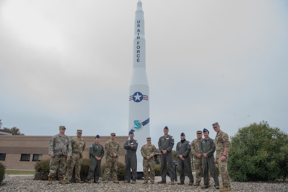 TOP HAND members pose for a photo in front of a Minuteman II missile display.