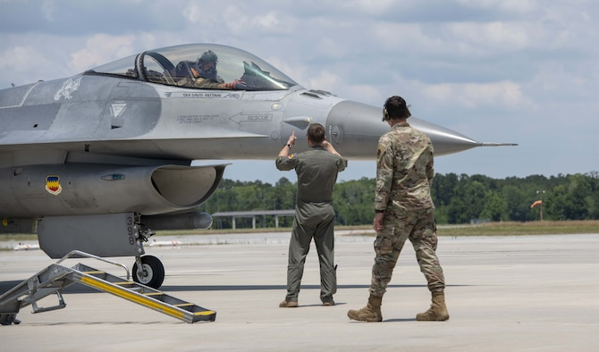 A photo of Airmen marshalling a jet.