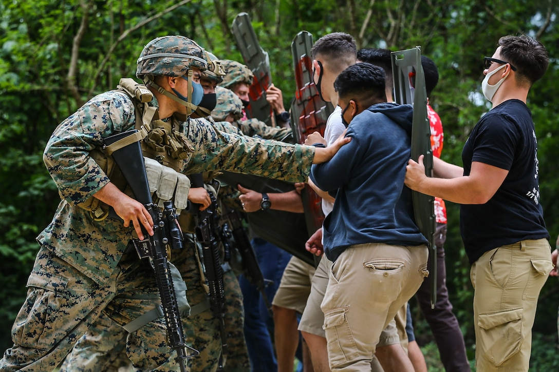 U.S. Marines with 9th Engineer Support Battalion, 3d Marine Logistics Group, warn notional protestors to move back using appropriate escalation of force tactics during exercise Pacific Pioneer, Okinawa, Japan, April 21, 2021. Pacific Pioneer serves as 9th ESB's Marine Corps Combat Readiness Evaluation as well as an opportunity to demonstrate the ability to establish and sustain expeditionary advanced bases with survivable force protection, practice naval integration, and position long range precision fires and tactical logistics nodes across littoral regions in support of naval operations. 3d MLG, based out of Okinawa, Japan, is a forward deployed combat unit that serves as III MEF's comprehensive logistics and combat service support backbone for operations throughout the Indo-Pacific area of responsibility. (U.S. Marine Corps photo by Sgt. Hailey D. Clay)