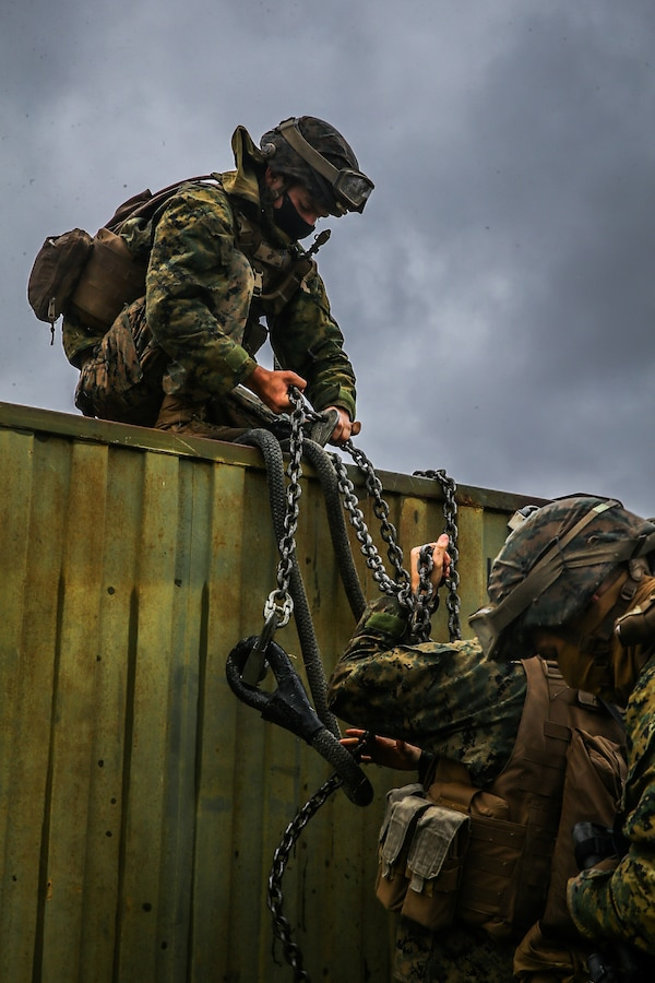 U.S. Marines with Landing Support Battalion, Combat Logistics Regiment 3, 3d Marine Logistics Group, prepare a quadcon to be attached to and transported by a CH-53 Super Stallion during exercise Pacific Pioneer at Torii Station, Okinawa, Japan, April 22, 2021. Pacific Pioneer serves as 9th Engineer Support Battalion's Marine Corps Combat Readiness Evaluation as well as an opportunity to demonstrate the ability to establish and sustain expeditionary advanced bases with survivable force protection, practice naval integration, and position long range precision fires and tactical logistics nodes across littoral regions in support of naval operations. 3d MLG, based out of Okinawa, Japan, is a forward deployed combat unit that serves as III MEF's comprehensive logistics and combat service support backbone for operations throughout the Indo-Pacific area of responsibility. (U.S. Marine Corps photo by Sgt. Hailey D. Clay)