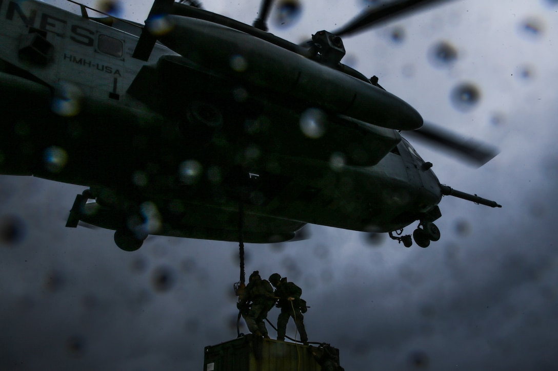 U.S. Marines with a Helicopter Support Team, Landing Support Battalion, Combat Logistics Regiment 3, 3d Marine Logistics Group, attach a quadcon to a CH-53 Super Stallion for transportation during exercise Pacific Pioneer at Torii Station, Okinawa, Japan, April 22, 2021. Pacific Pioneer serves as 9th Engineer Support Battalion's Marine Corps Combat Readiness Evaluation as well as an opportunity to demonstrate the ability to establish and sustain expeditionary advanced bases with survivable force protection, practice naval integration, and position long range precision fires and tactical logistics nodes across littoral regions in support of naval operations. 3d MLG, based out of Okinawa, Japan, is a forward deployed combat unit that serves as III MEF's comprehensive logistics and combat service support backbone for operations throughout the Indo-Pacific area of responsibility. (U.S. Marine Corps photo by Sgt. Hailey D. Clay)