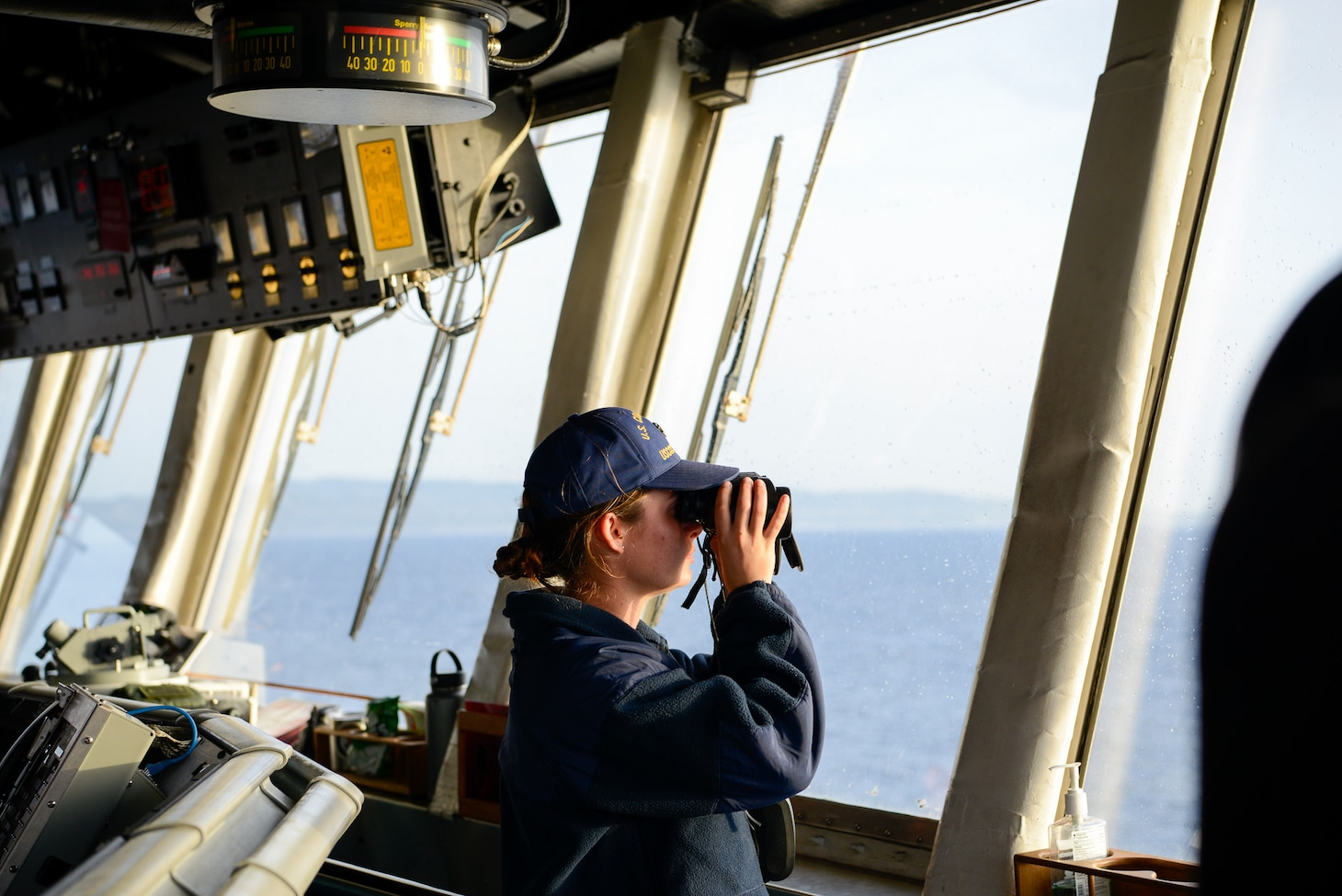 210522-G-ID129-4064 MEDITERRANEAN SEA (May 22, 2021) Seaman Cheyenne Solis Headlam looks out from the bridge as they transit out of the Mediterranean Sea, May 22, 2021. Hamilton is on a routine deployment in the U.S. Sixth Fleet area of operations in support of U.S. national interests and security in Europe and Africa. (U.S. Coast Guard photo by Petty Officer 3rd Class Sydney Phoenix)