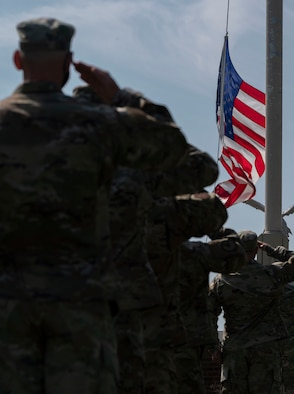 The Team Dover Chief's Group and First Sgt. Council salute the flag during a retreat ceremony at Dover Air Force Base, Delaware, May 20, 2021. Retreat is used to pay respects to the flag and signifies the end of the duty day. (U.S. Air Force photo by Airman 1st Class Cydney Lee)
