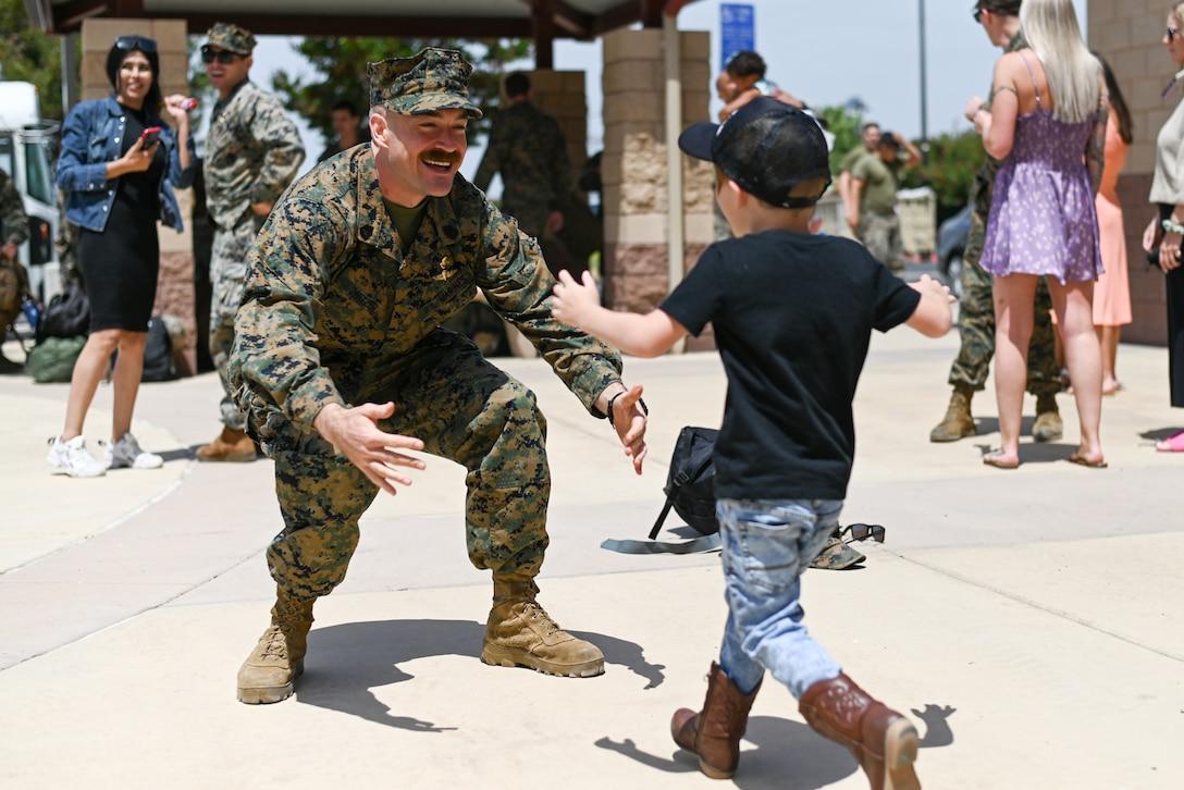 A small boy runs toward a waiting Marine.