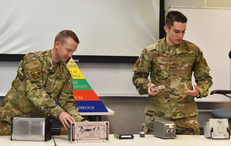 Tech. Sgt. Seth Rutt, 341st Operations Support Squadron nuclear cryptographic controller, left, and Capt. Alexander Garland, 341st OSS nuclear cryptographic operator, examine nuclear launch code training equipment May 19, 2021, on Malmstrom Air Force Base, Mont. In order to launch a missile there are various steps that must be verified by using the shown equipment. (U.S. Air Force photo by Tech. Sgt. Joseph Park)