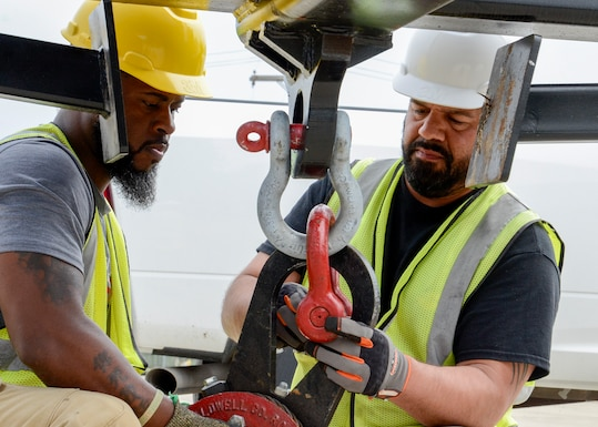 Two men hook up a sling for heavy equipment lifting.