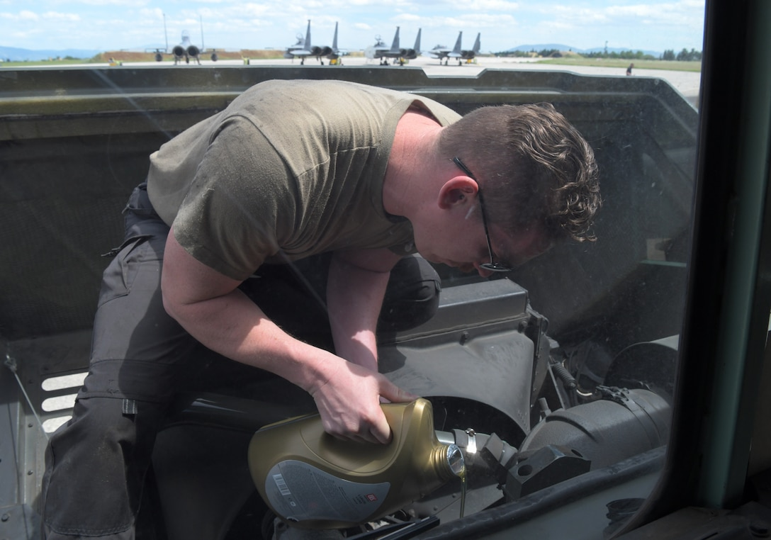 U.S. Air Force Staff Sgt. Kevin Grimm, 48th Logistics Readiness Squadron vehicle maintenance craftsman, tops off the oil on a refueling truck during exercise Astral Knight 21 at Larissa Air Base, Greece, May 20, 2021. During Astral Knight 21, the Liberty Wing sharpened its ability to deploy capable, credible forces to operate from strategic locations, which is enabled by strong regional partnerships critical for a rapid united response to adversaries around the world. (U.S. Air Force photo by Tech. Sgt. Alex Fox Echols III)