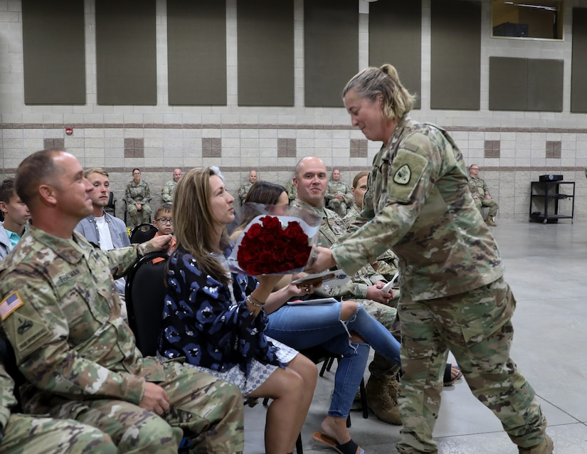 Soldier gives red roses to spouse of outgoing command sergeant major during a change of responsibility cereemony
