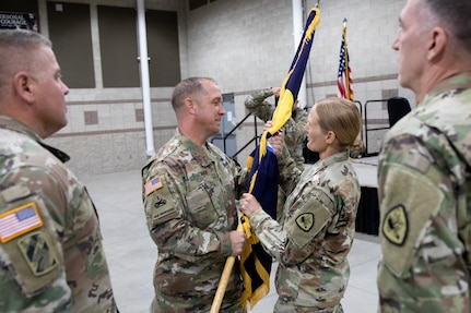Soldiers pass the organizational colors during a change of command ceremony.