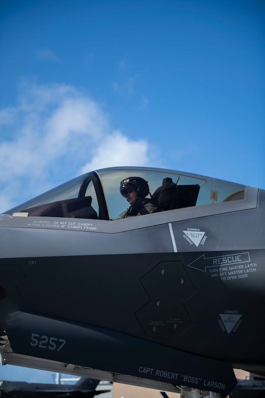 Side view of a man sitting in the cockpit of a plane