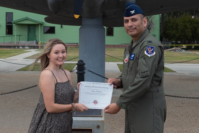 Airmen hands paper to military dependent.