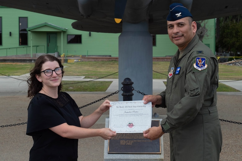 Airmen hands paper to military spouse.