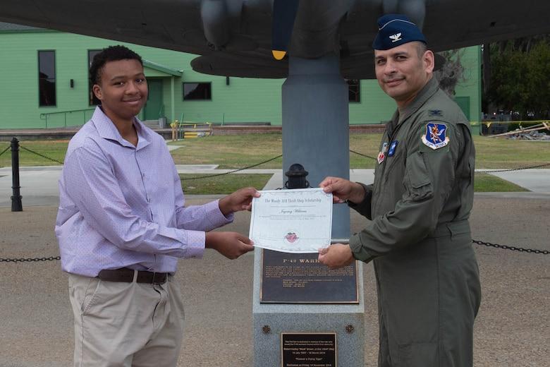 Airmen hands paper to high school student.