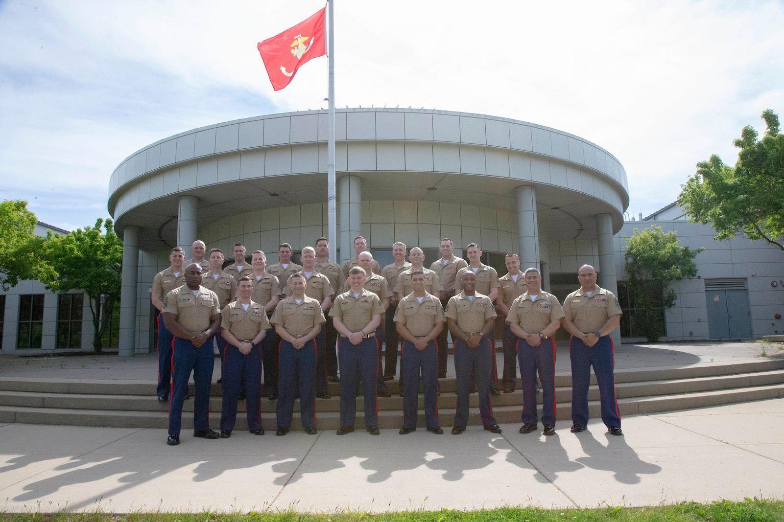 U.S. Marines from 9th Marine Corps District pose for a photo after graduating from the Staff Non-Commissioned Officer in Charge course 3-21 on Naval Station Great Lakes, Ill., May 21, 2021. The course teaches the Marines how to properly lead their respective recruiting sub-stations. (U.S. Marine Corps illustration by Cpl. Baylee Boggs)