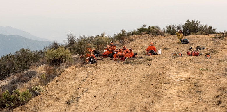 California Department of Corrections inmate fire fighters rest after clearing a fire line near Santa Barbara, California, Dec 11, 2017. The inmates were brought in to help fight the Thomas Fire. The fire started on Dec. 4, 2017 in Santa Paula, near Thomas Aquinas College. Driven by Santa Ana winds gusting up to 70 mph, the flames screamed across the hillsides toward Ojai, Ventura and Santa Barbara. (U.S. Air Force photo/Master Sgt. Brian Ferguson)