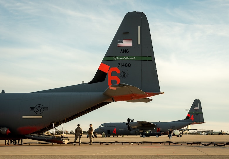 Two C-130Js of the 146th Airlift Wing, which carry the Modular Airborne Fire Fighting System, are reloaded with flame retardant chemicals at Channel Islands Air National Guard Base in Port Hueneme, California, in preparation for operations to contain the Thomas wildfire burning in Ventura and Santa Barbara Counties, Dec. 9, 2017. (U.S. Air Force photo by J.M. Eddins Jr.)