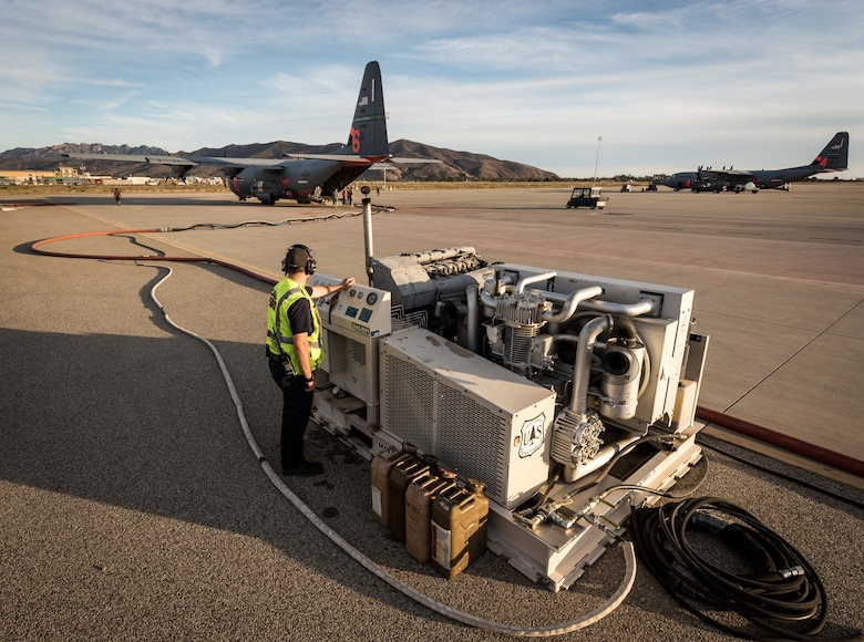 A fuels technician runs a pump fueling a C-130J of the 146th Airlift Wing on the flightline at Channel Islands Air National Guard Base in Port Hueneme, California, Dec. 9, 2017. It takes just 15-20 minutes to pump a mixture of dry chemicals and water into the storage tank of the MAFFS unit, which is loaded in the cargo bay, and launch the aircraft on another fire-fighting sortie. (U.S. Air Force photo by J.M. Eddins Jr.)
