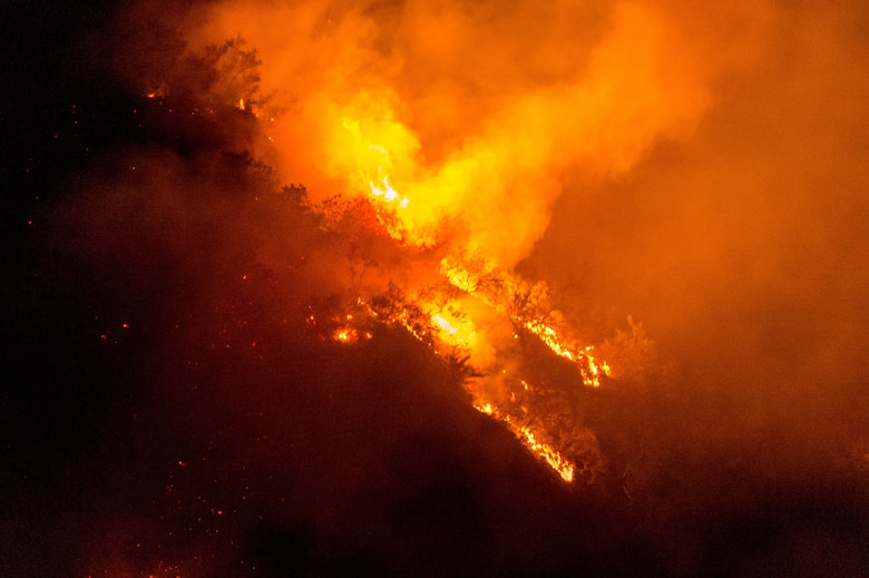 The Thomas Fire, named for the fire's point of origin near St. Thomas Aquinas College in Santa Paula, California, burns on a ridgeline in Santa Barbara County, Dec. 10, 2017. The fire, initially fanned by 80-mph Santa Ana winds, quickly spread across the Los Padres National Forest in Ventura and Santa Barbara counties. (U.S. Air Force photo by J.M. Eddins Jr.)