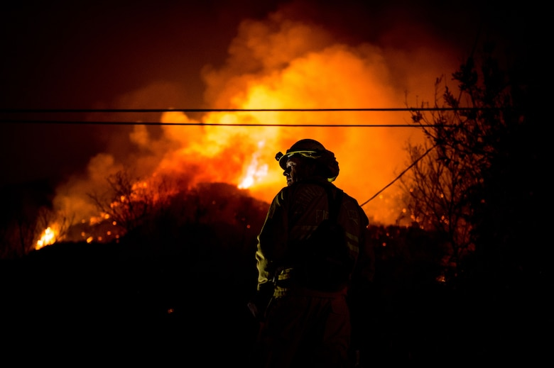 Chino Valley firefighters watch the oncoming flames of the Thomas Fire from the yard of a home in Montecito, California, Dec. 12, 2017. C-130Js of the 146th Airlift Wing at Channel Islands Air National Guard Base in Port Hueneme, carried the Modular Airborne Fire Fighting System and dropped fire suppression chemicals onto the fire's path to slow its advance in support of firefighters on the ground. (U.S. Air Force photo by J.M. Eddins Jr.)