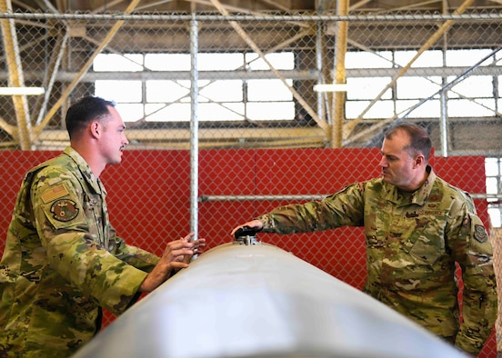 Senior Airman Christian Landerman (left), 92nd Maintenance Squadron hydraulics journeyman, talks to U.S. Air Force Maj. Gen. Thad Bibb (right), about a refueling pod in the 92nd MXS during a base tour on Fairchild Air Force Base, Washington, May 19-21, 2021.