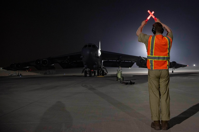 A military aircraft taxis on an airfield.  A man uses a light to direct the aircraft.