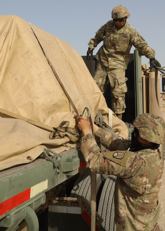 A man in a military uniform adjusts straps that are wrapped around a tarp-covered load on a truck.  Another man in a military uniform stands on the bed of the truck.