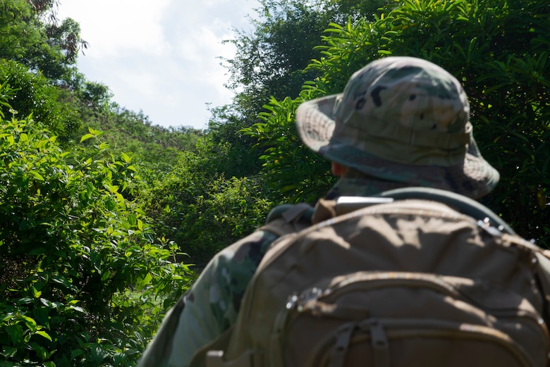 Tech. Sgt. Adam Rogers assigned to the 36th Security Forces Squadron performs a ground tasking operation overlooking a cliff face searching for signs of human activity along the eastern shoreline on Andersen Air Force Base, Guam May 14 2021. Andersen Air Force Base covers 14,600 acres, more than half of which is undeveloped land. (U.S. Air Force photo by SSgt Nicholas Crisp)