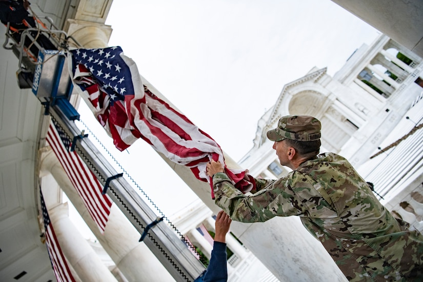 A service member hangs a flag on a building.