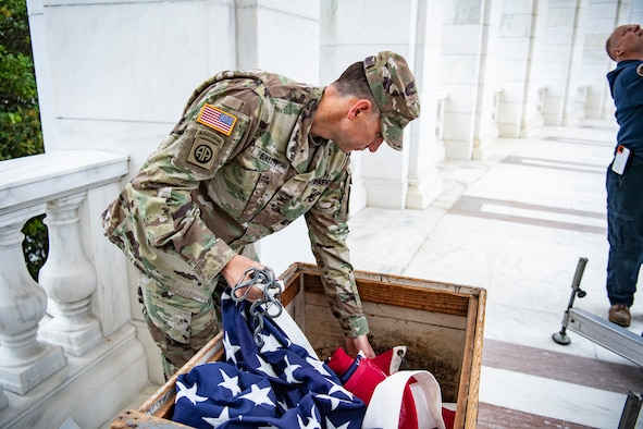 A soldier takes an American flag out of a box.
