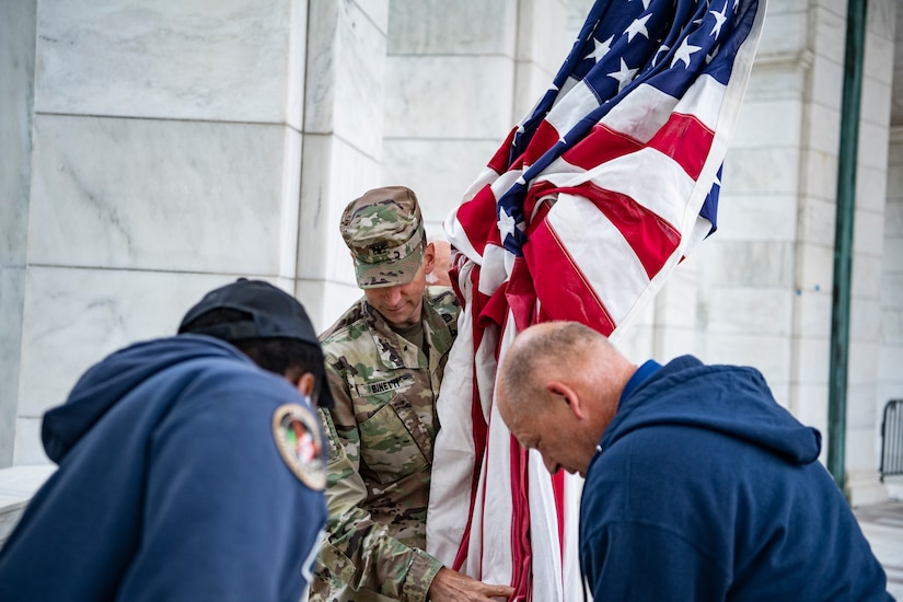 A service member carries an American flag.